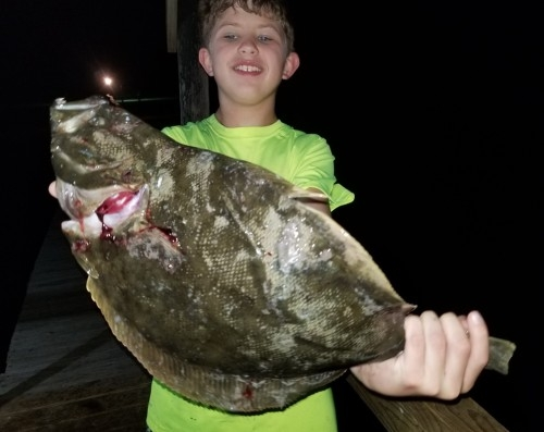 BOY WITH LARGE FLOUNDER